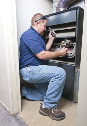 technician-inspecting-inside-of-furnace